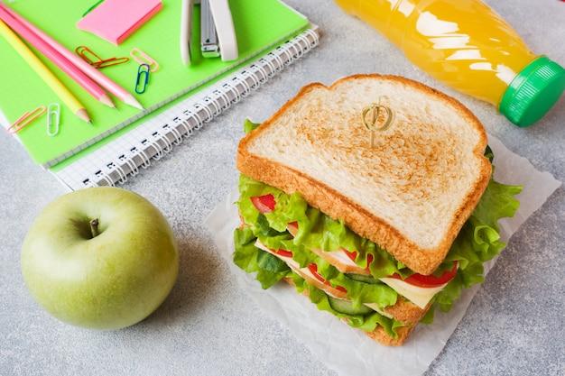 サンドイッチ、新鮮なリンゴ、オレンジジュースを使ったヘルシーなランチ。 Premium写真