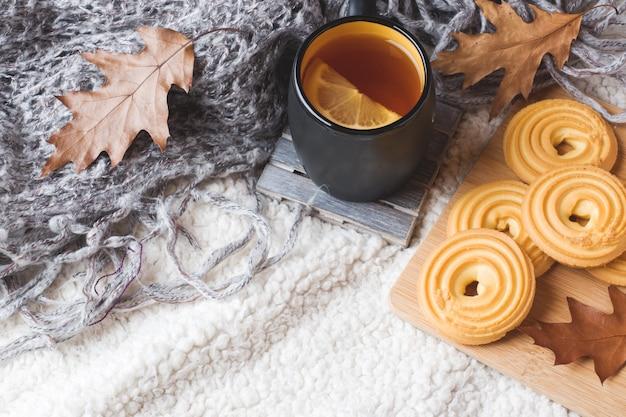 紅茶、クッキー、セーター、暖かい柔らかい毛布の上の葉の秋のある静物。 Premium写真
