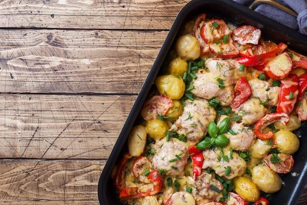 木製のテーブルの上のベーキングトレイに焼かれた鶏もも、ジャガイモ、野菜 Premium写真