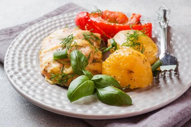 プレート上の野菜とチキンのベイクドポテト Premium写真