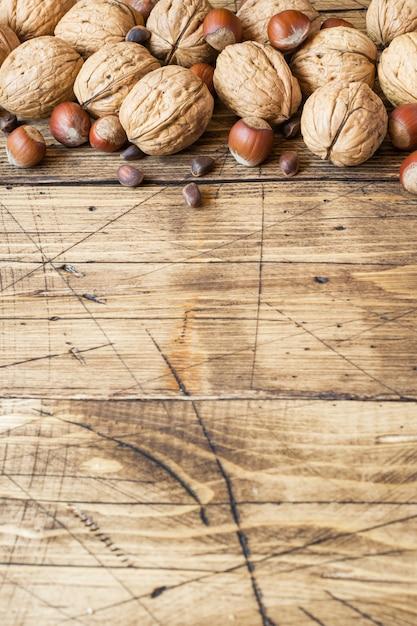 クルミ、ヘーゼルナッツ、古い木造の暗い面の杉。 Premium写真