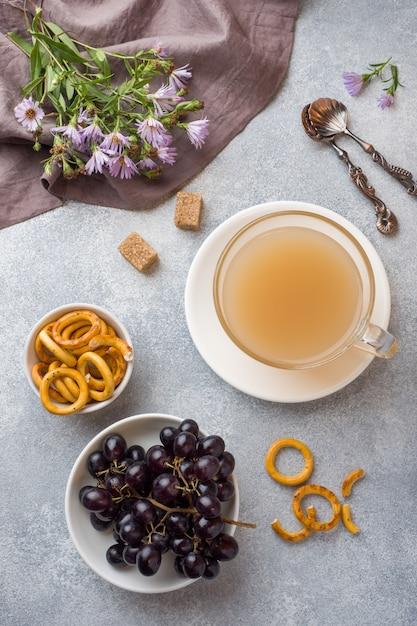 ミルクとグレーのテーブルのクラッカーとコーヒーのカップ。 Premium写真