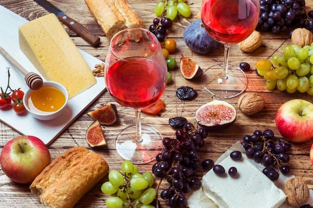 素朴な木製のテーブルの上にチーズ、ワイン、バゲットグレープが蜂蜜と軽食を添えています。 Premium写真