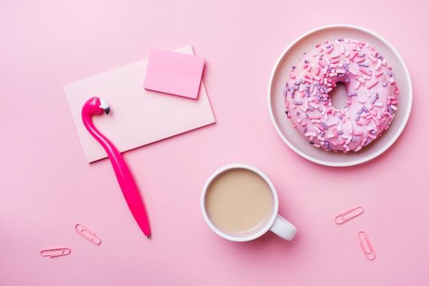 Чашка кофе, пончик перо фламинго блокнот на розовый. концепция офиса. квартира лежала. Premium Фотографии