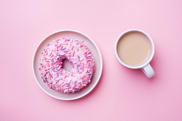 一杯のコーヒーとピンクのドーナツ。トップビューフラット Premium写真
