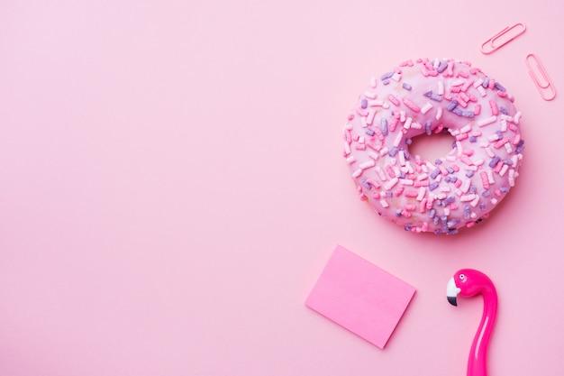 ピンクのドーナツとピンクのフラミンゴペン。トップビューフラット Premium写真