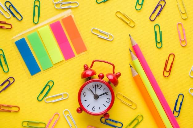 鉛筆とカラーペーパークリップ、時計のアラーム Premium写真