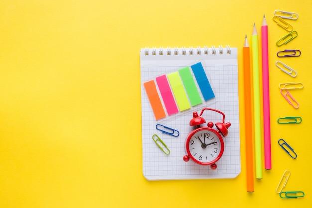 ノートブック、鉛筆と色紙クリップ、黄色の時計アラーム Premium写真