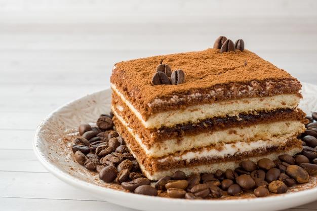 Вкусный торт тирамису с кофейными зернами на тарелке на свет Premium Фотографии