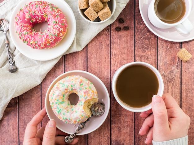 ドーナツと木製のテーブルの上のコーヒー。コピースペース平面図。 Premium写真