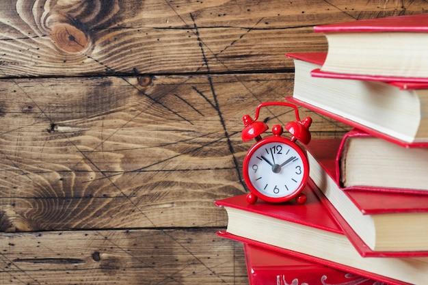 ハードカバーの本と木製のテーブルの上の目覚まし時計のスタック。テキストのコピースペース Premium写真