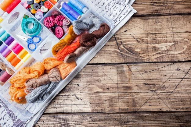 テーブルの上にハサミで針仕事色の糸、センチメートルとボタンのための裁縫道具 Premium写真