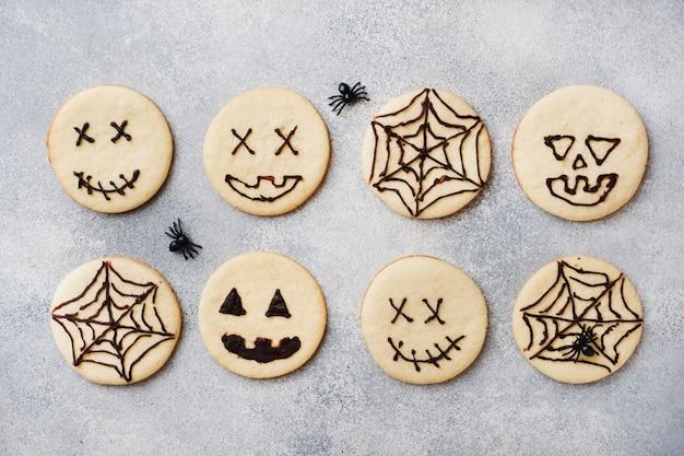 ハロウィーン用の自家製クッキー、変な顔のクッキー、クモの巣 Premium写真
