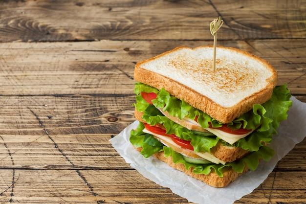 暗い木製のテーブルにおいしいと新鮮なサンドイッチ。 Premium写真