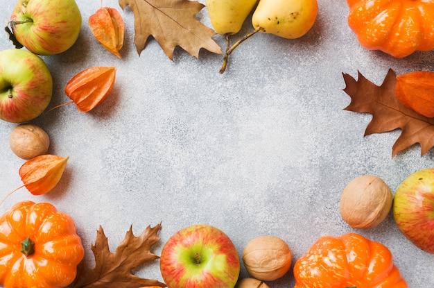 黄色の葉、カボチャりんご梨、ナッツと秋の背景 Premium写真