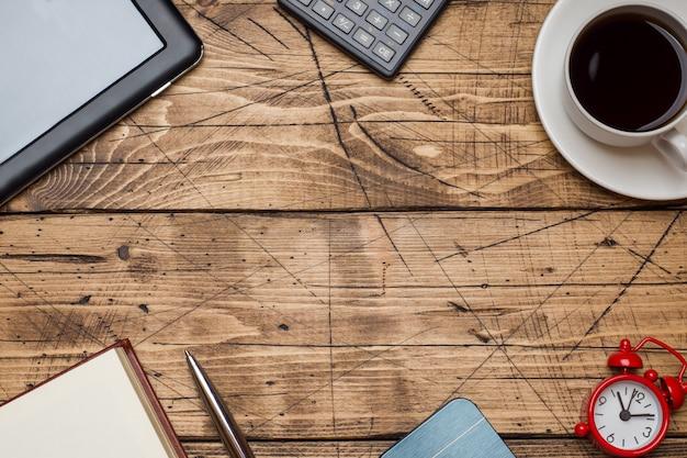 テキストと木製の背景にコーヒーカップのメモ帳 Premium写真
