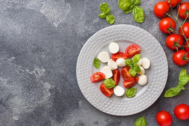 トマト、モッツァレラチーズ、バジルのカプレーゼサラダ。イタリア料理。 Premium写真
