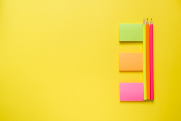 コピースペースを持つ黄色のテーブルに事務用品。 Premium写真