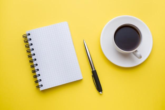 テキストとコピースペースと黄色いコーヒーカップのメモ帳。教育およびオフィスのコンセプト Premium写真