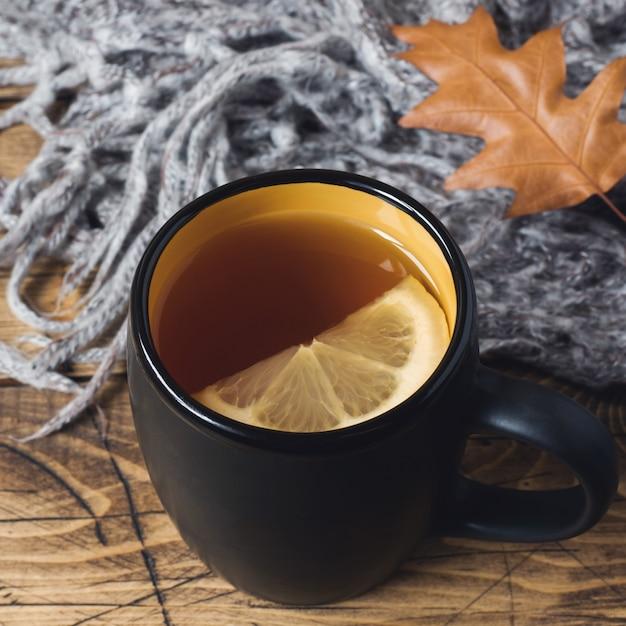 木製のテーブルにお茶、暖かい毛布、黄色の葉。 Premium写真