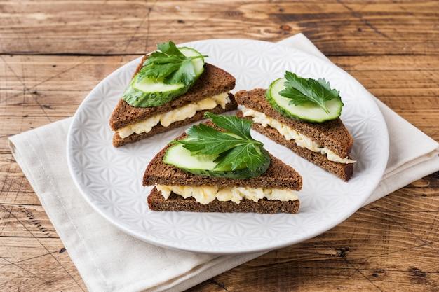 スクランブルエッグと木製の素朴な背景にキュウリのサンドイッチ Premium写真