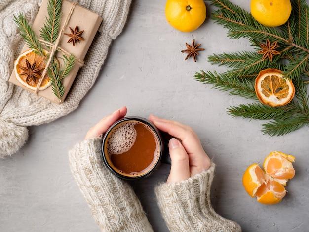 Зимой горячий напиток женских рук в кофте держит чашку горячего шоколада Premium Фотографии