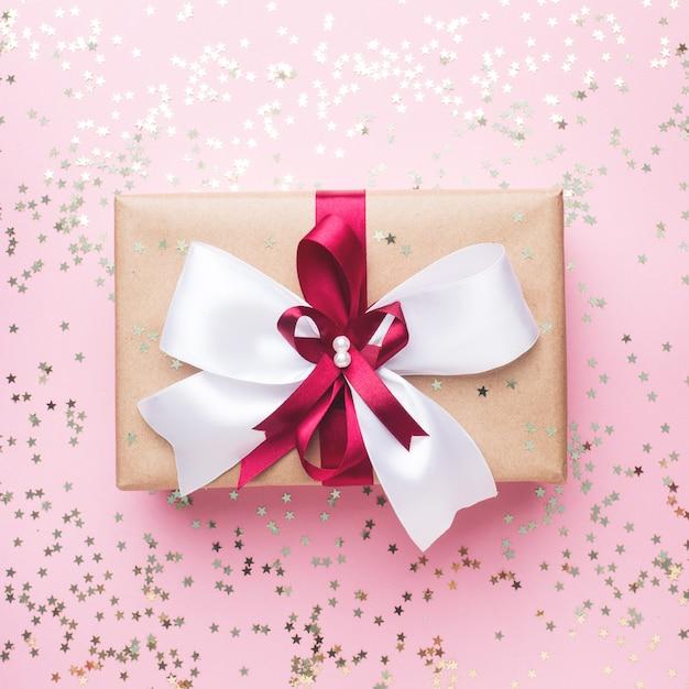 ピンクのテーブルトップビューに大きな弓のギフトボックスまたはプレゼントボックス。クリスマス、誕生日、母の日、結婚式のフラットレイアウト構成。 Premium写真