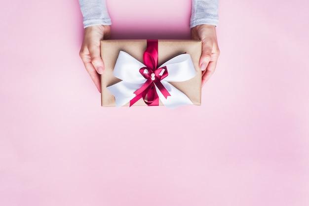 ピンクのテーブルの上の女性の手に大きな弓でギフトまたはプレゼントボックス。クリスマス、誕生日、母の日、結婚式のフラットレイアウト構成。 Premium写真