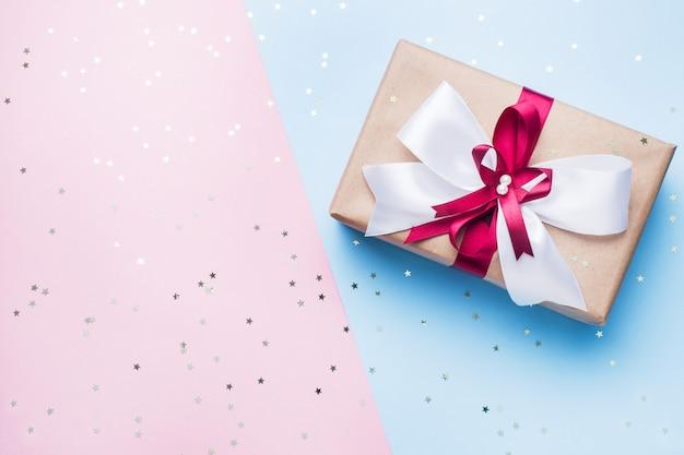 ピンクブルーのテーブルトップビューに大きな弓でギフトまたはプレゼントボックス。クリスマス、誕生日、母の日、結婚式のフラットレイアウト構成。 Premium写真
