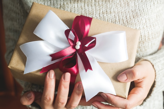 Подарочная или подарочная коробка с большим бантом в руках женщины в свитере. композиция на рождество, день рождения, день матери или свадьбу. Premium Фотографии