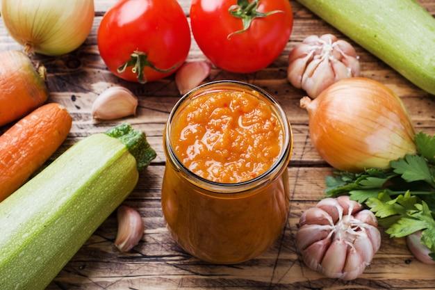 木製のガラス瓶にズッキーニトマトとタマネギの自家製キャビア。自家製の生産缶詰、缶詰シチュー野菜。 Premium写真