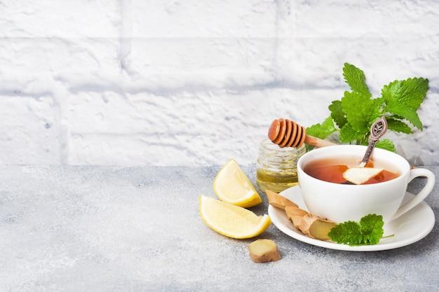 Белая чашка с натуральным травяным чаем, имбирем, лимонной мятой и медом. Premium Фотографии