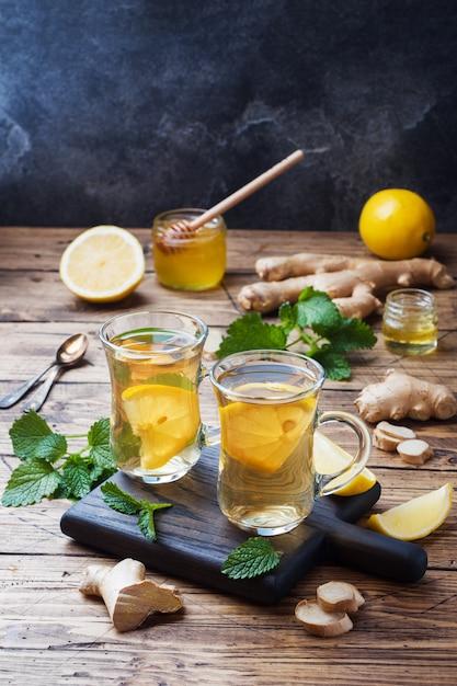 Две чашки натурального травяного чая, имбирь, лимон, мята и мед копирование пространства Premium Фотографии