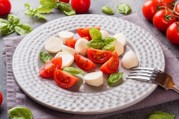 暗い背景にトマト、モッツァレラチーズ、バジルのカプレーゼサラダ。イタリア料理。 Premium写真