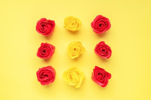 黄色の背景に赤と黄色のバラのつぼみ。バレンタインの日、結婚式のロマンスの概念。フラットレイアウトコピースペース。 Premium写真