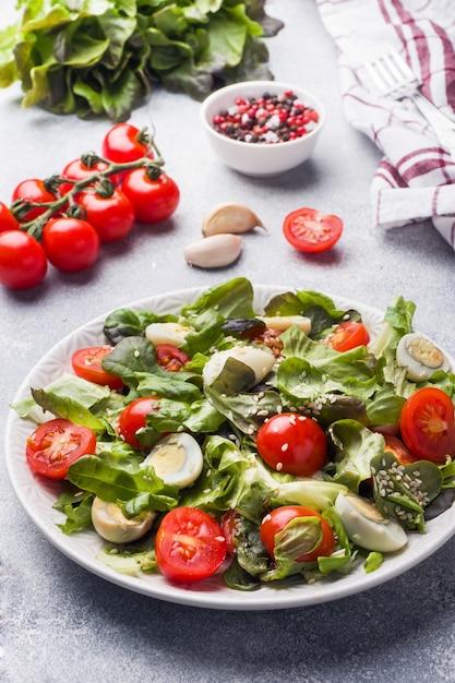 Свежий салат с помидорами и перепелиными яйцами и листьями салата. Premium Фотографии