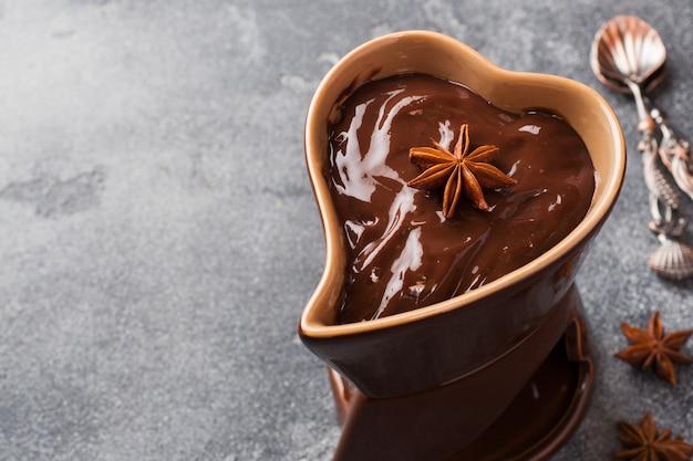 Шоколадная паста с корицей и анисом. фондю с шоколадом на темном бетонном столе. копировать пространство Premium Фотографии