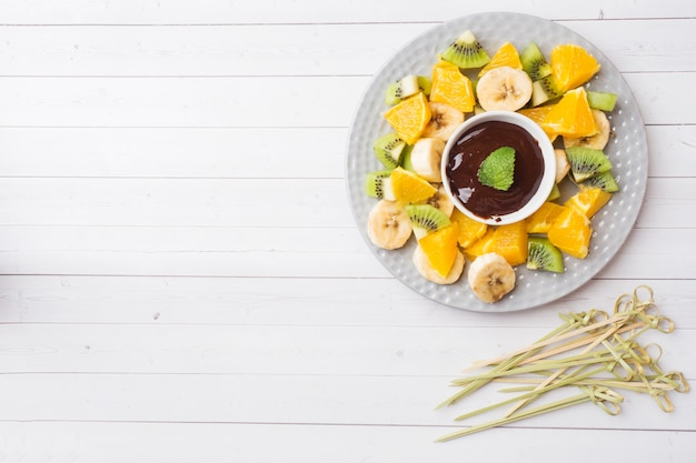 Шоколадное фондю с фруктами на белом столе. концепция летней вечеринки. копировать пространство Premium Фотографии