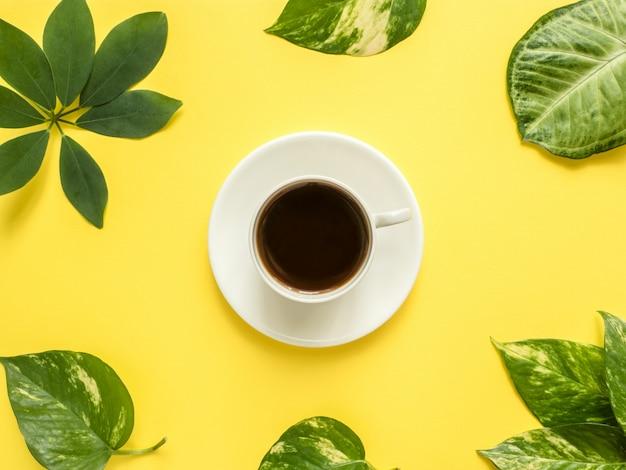 緑の葉と黄色の背景の中央に一杯のコーヒー。 Premium写真