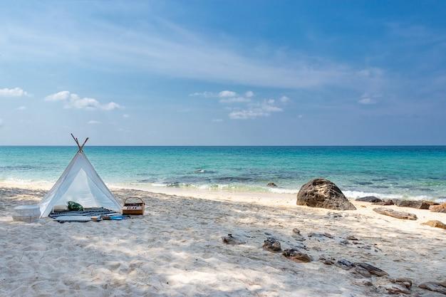 澄んだ水と青い空と白い砂浜にロマンチックな白いピクニックテント Premium写真