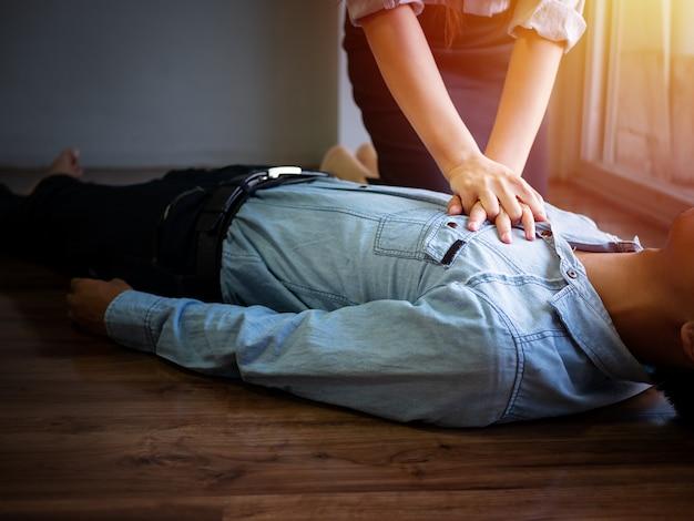 Женщина-волонтер, работающая в офисе, использует ручной насос на груди для оказания неотложной помощи. Premium Фотографии
