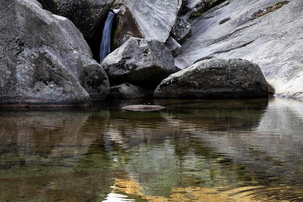 石の間を通過するときに川によって作成された小さな急な滝 Premium写真
