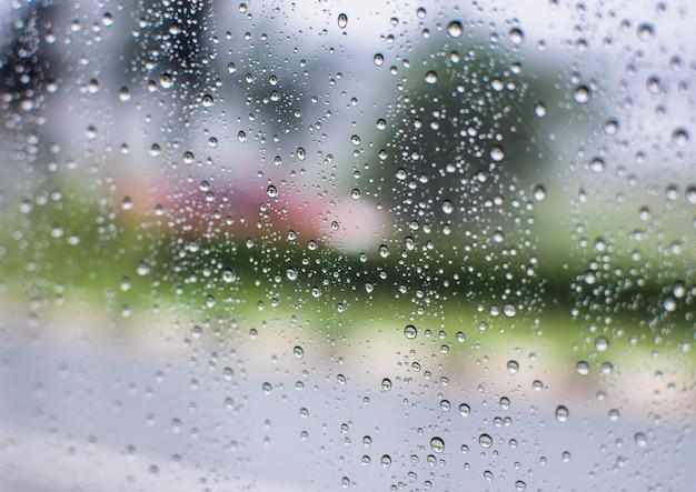 Капли дождевой воды и текст на окне с абстрактным размытия фона Premium Фотографии