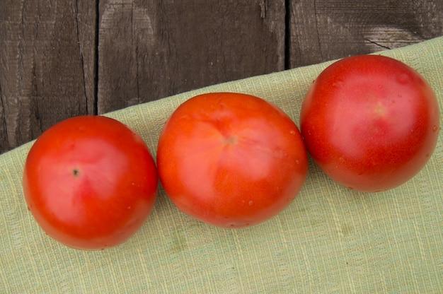Свежие, спелые помидоры на салфетке, темный деревянный фон Premium Фотографии