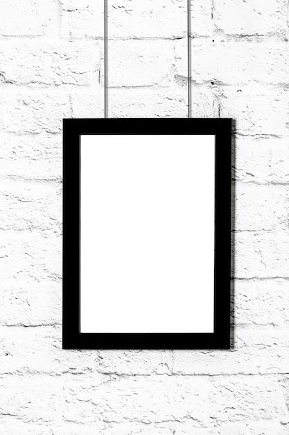 Вертикальная черная рамка для фотографий, висящая на кирпичной стене. макет с копией пространства. Premium Фотографии