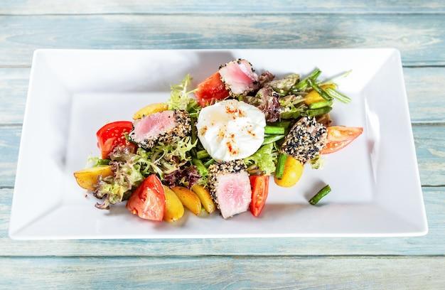 Салат нисуаз с жареным тунцом и яйцом-пашот Premium Фотографии