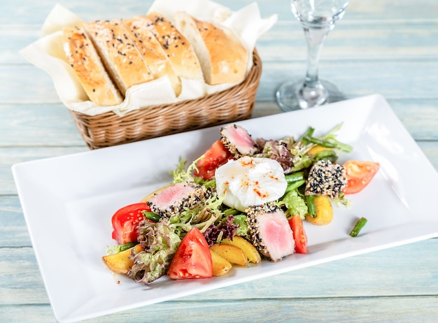 ニース風サラダ、マグロのローストと半熟卵の木製テーブル Premium写真
