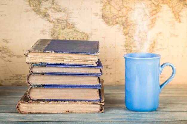 古書のスタックと温かい飲み物のカップ。マップの背景 Premium写真