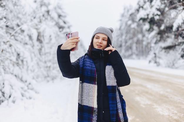 Красивая девушка делает селфи посреди снежной лесной дороги Premium Фотографии