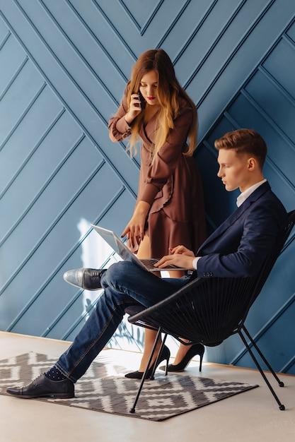 ラップトップと電話を持つ少女一緒にスタイリッシュな若い男、青年実業家 Premium写真
